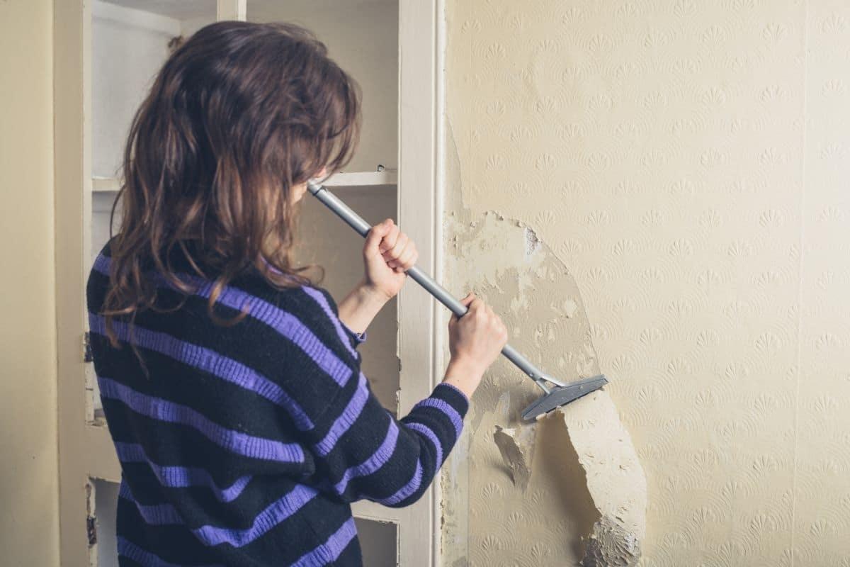woman scrapes wallpaper off wall