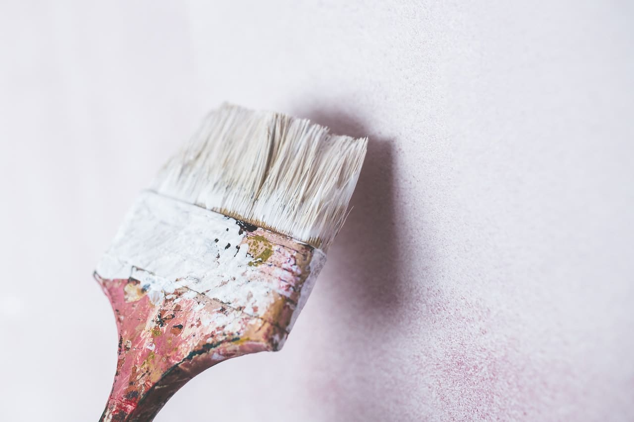 painting a wall with paint brush and white paint