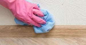 gloved-hand-wiping-wall-with-cloth