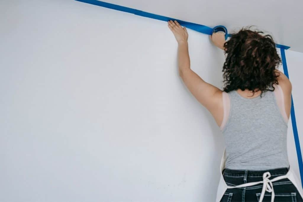 woman applies painters tape to ceiling