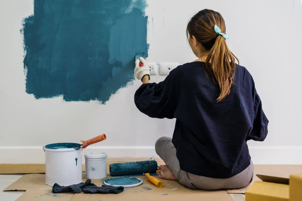 woman sites on floor and paints walls