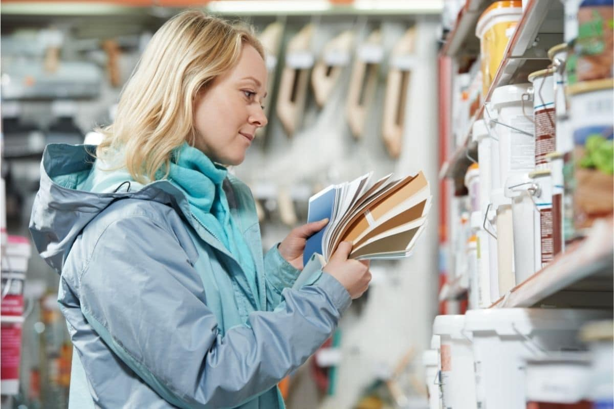 women chooses house paint at hardware store