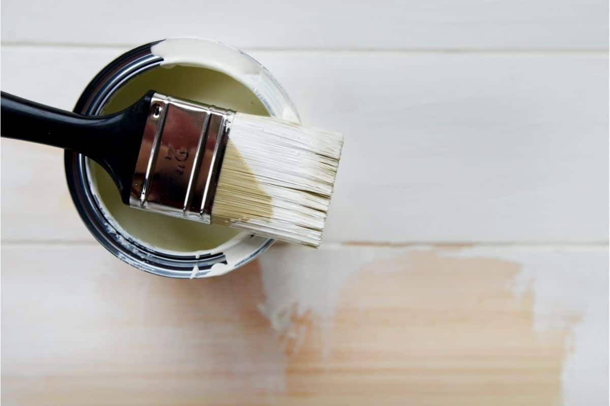 paint brush resting on paint can